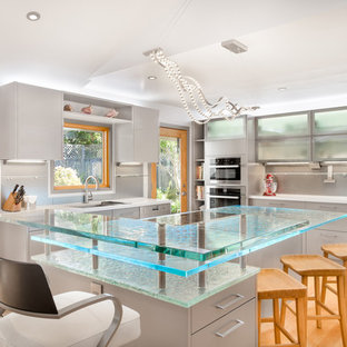 Photo of a large contemporary u-shaped kitchen in Los Angeles with flat-panel cabinets, glass worktops, stainless steel appliances, light hardwood flooring, a submerged sink, grey cabinets, grey splashback, an island and turquoise worktops.