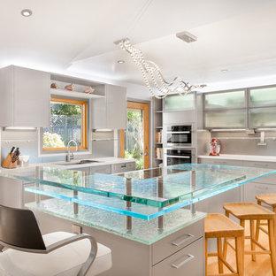 Modern inredning av ett stort turkos turkost u-kök, med släta luckor, bänkskiva i glas, rostfria vitvaror, ljust trägolv, en undermonterad diskho, grå skåp, grått stänkskydd och en köksö
