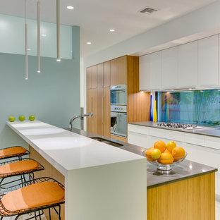Esempio di una cucina design con lavello a doppia vasca, ante lisce, elettrodomestici in acciaio inossidabile e penisola
