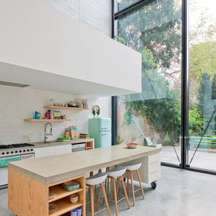 Design ideas for a large contemporary single-wall eat-in kitchen in Other with an integrated sink, flat-panel cabinets, white cabinets, concrete benchtops, white splashback, coloured appliances, concrete floors and with island.
