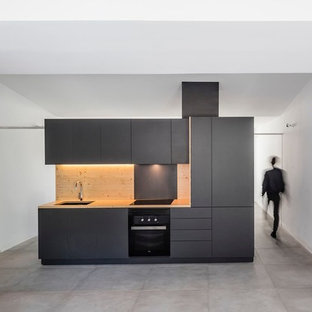 Small contemporary open concept kitchen photos - Example of a small trendy single-wall ceramic floor open concept kitchen design in London with an undermount sink, flat-panel cabinets, black cabinets, wood countertops, brown backsplash, black appliances and no island