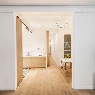 Modelo de cocina comedor en L, actual, pequeña, sin isla, con armarios con paneles lisos, puertas de armario de madera oscura, salpicadero blanco y suelo de madera en tonos medios