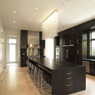 Contemporary kitchen pictures - Example of a trendy kitchen design in Atlanta with paneled appliances, flat-panel cabinets, black cabinets and granite countertops