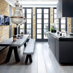 Design ideas for a medium sized contemporary kitchen/diner in London with flat-panel cabinets, black cabinets, composite countertops, dark hardwood flooring, an island, brown floors and a double-bowl sink.