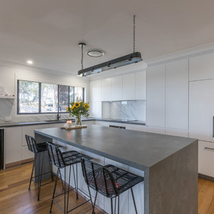 This is an example of a contemporary l-shaped kitchen in Sydney with an undermount sink, flat-panel cabinets, white cabinets, white splashback, stainless steel appliances, medium hardwood floors, with island, brown floor and grey benchtop.