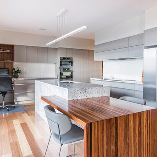 Design ideas for a contemporary l-shaped eat-in kitchen in Hobart with an undermount sink, flat-panel cabinets, grey cabinets, white splashback, glass sheet splashback, stainless steel appliances, light hardwood floors, an island, brown floor and grey benchtop.