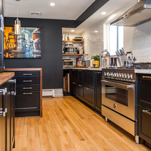 This is an example of a mid-sized contemporary galley separate kitchen in New York with an undermount sink, recessed-panel cabinets, black cabinets, wood benchtops, white splashback, stainless steel appliances, with island, brown benchtop, subway tile splashback, light hardwood floors and beige floor.