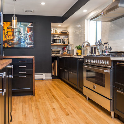 Enclosed kitchen - mid-sized contemporary galley light wood floor and beige floor enclosed kitchen idea in New York with an undermount sink, recessed-panel cabinets, black cabinets, wood countertops, white backsplash, stainless steel appliances, an island, brown countertops and subway tile backsplash