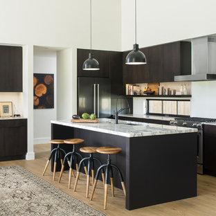 Idee per una cucina parallela minimal con lavello sottopiano, ante lisce, ante in legno bruno, elettrodomestici in acciaio inossidabile, pavimento in legno massello medio, isola e pavimento marrone