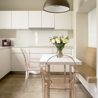 Photo of a contemporary kitchen/diner in London with flat-panel cabinets, white cabinets, white splashback, glass sheet splashback, travertine flooring and beige floors.
