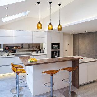 Große Moderne Küche mit flächenbündigen Schrankfronten, weißen Schränken, Küchenrückwand in Metallic, Rückwand aus Spiegelfliesen und Kücheninsel in Hertfordshire