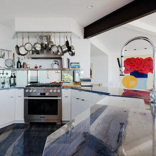 サンフランシスコの中サイズのコンテンポラリースタイルのおしゃれなキッチン (エプロンフロントシンク、フラットパネル扉のキャビネット、白いキャビネット、珪岩カウンター、メタリックのキッチンパネル、ミラータイルのキッチンパネル、シルバーの調理設備、大理石の床、アイランドなし、青い床、青いキッチンカウンター) の写真