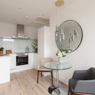 Design ideas for a contemporary u-shaped open plan kitchen in London with a submerged sink, flat-panel cabinets, white cabinets, glass sheet splashback, light hardwood flooring and beige floors.