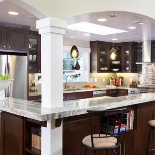 Esempio di una cucina a L design con elettrodomestici in acciaio inossidabile, ante di vetro, ante in legno bruno, top in quarzite, paraspruzzi con piastrelle a listelli e paraspruzzi multicolore