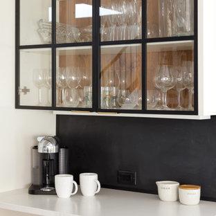ニューヨークの小さいコンテンポラリースタイルのおしゃれなキッチン (アンダーカウンターシンク、フラットパネル扉のキャビネット、白いキャビネット、クオーツストーンカウンター、レンガのキッチンパネル、シルバーの調理設備の、淡色無垢フローリング、白いキッチンカウンター) の写真