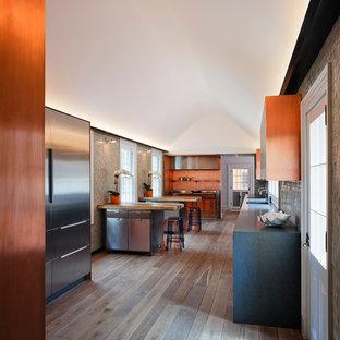 Modelo de cocina contemporánea con salpicadero naranja y electrodomésticos de acero inoxidable
