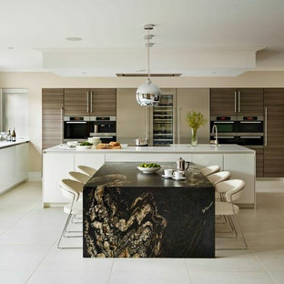 Bild på ett stort funkis kök och matrum, med släta luckor, vita skåp, en köksö och integrerade vitvaror
