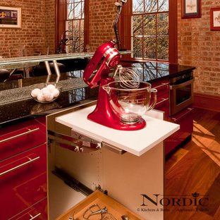Photo of a mid-sized contemporary single-wall eat-in kitchen in New Orleans with an undermount sink, flat-panel cabinets, red cabinets, granite benchtops, panelled appliances, beige splashback, glass tile splashback, dark hardwood floors and with island.