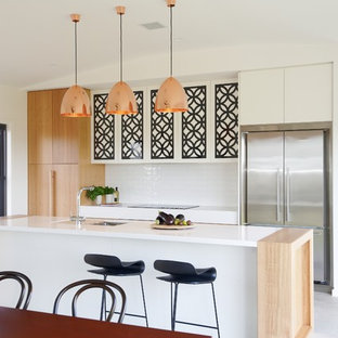 Design ideas for a contemporary galley open plan kitchen in Sydney with flat-panel cabinets, white cabinets, white splashback, stainless steel appliances, concrete floors, with island, grey floor and white benchtop.