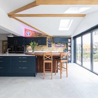 Immagine di una cucina parallela classica di medie dimensioni con ante lisce, isola, pavimento grigio e ante blu