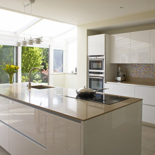 Kitchen - contemporary galley kitchen idea in Dublin with mosaic tile backsplash, multicolored backsplash, paneled appliances, an undermount sink, white cabinets, flat-panel cabinets and brown countertops