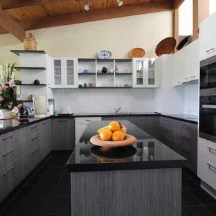 メルボルンの広いコンテンポラリースタイルのおしゃれなキッチン (ドロップインシンク、フラットパネル扉のキャビネット、グレーのキャビネット、御影石カウンター、白いキッチンパネル、ガラス板のキッチンパネル、シルバーの調理設備、スレートの床) の写真