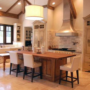 Contemporary single-wall open plan kitchen in Sacramento with a farmhouse sink, raised-panel cabinets, beige cabinets, zinc benchtops, grey splashback, stone tile splashback, panelled appliances, travertine floors and with island.
