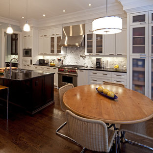 Example of a trendy kitchen design in Toronto with stainless steel appliances, a double-bowl sink, glass-front cabinets, white cabinets, white backsplash and stone tile backsplash