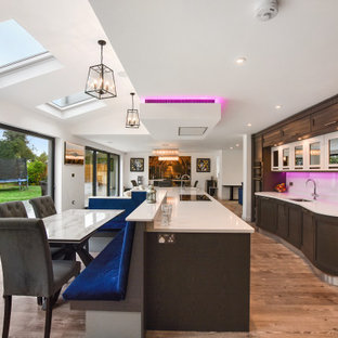 Expansive contemporary galley kitchen/diner in London with a submerged sink, shaker cabinets, medium wood cabinets, white splashback, stainless steel appliances, an island, brown floors and beige worktops.