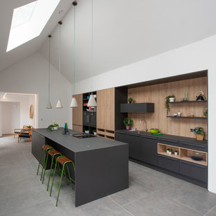 Design ideas for a contemporary l-shaped kitchen in West Midlands with a submerged sink, flat-panel cabinets, grey cabinets, brown splashback, wood splashback, integrated appliances, grey floors and grey worktops.