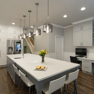 This is an example of a medium sized industrial l-shaped open plan kitchen in Chicago with a submerged sink, shaker cabinets, white cabinets, engineered stone countertops, multi-coloured splashback, metro tiled splashback, stainless steel appliances, dark hardwood flooring and an island.