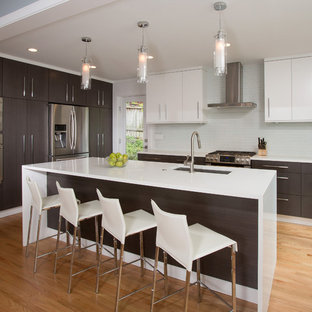 Design ideas for a mid-sized contemporary single-wall eat-in kitchen in DC Metro with an undermount sink, flat-panel cabinets, solid surface benchtops, white splashback, stainless steel appliances, with island, dark wood cabinets, glass tile splashback and light hardwood floors.