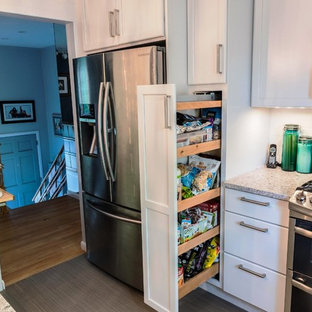 This is an example of a mid-sized contemporary l-shaped eat-in kitchen in New York with a farmhouse sink, shaker cabinets, white cabinets, quartz benchtops, white splashback, ceramic splashback, stainless steel appliances, porcelain floors and with island.