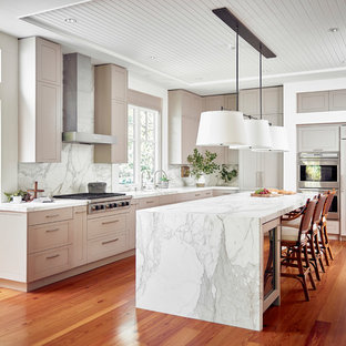 Photo of a large traditional l-shaped kitchen in Denver with recessed-panel cabinets, marble benchtops, white splashback, marble splashback, stainless steel appliances, medium hardwood floors, with island, beige cabinets and orange floor.