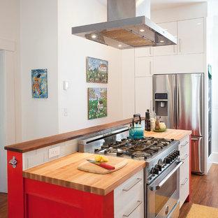 Foto de cocina actual con armarios con paneles lisos, puertas de armario rojas, encimera de madera, salpicadero blanco, salpicadero de azulejos tipo metro y electrodomésticos de acero inoxidable