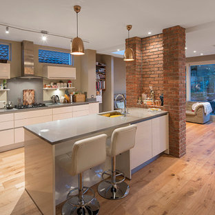 Inspiration for a contemporary single-wall open plan kitchen in Dublin with a submerged sink, flat-panel cabinets, white cabinets, composite countertops, grey splashback, stainless steel appliances, light hardwood flooring and a breakfast bar.