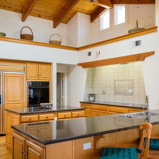 サンフランシスコの広いビーチスタイルのおしゃれなキッチン (ドロップインシンク、レイズドパネル扉のキャビネット、中間色木目調キャビネット、御影石カウンター、グレーのキッチンパネル、磁器タイルのキッチンパネル、パネルと同色の調理設備、無垢フローリング、茶色い床、黒いキッチンカウンター) の写真