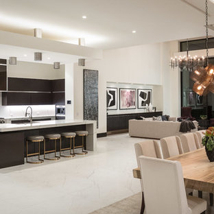 Contemporary open concept kitchen photos - Example of a trendy galley white floor open concept kitchen design in Orange County with flat-panel cabinets, dark wood cabinets, white backsplash, stone slab backsplash, stainless steel appliances, an island and white countertops