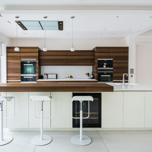 Photo of a medium sized contemporary galley kitchen in Cardiff with flat-panel cabinets, medium wood cabinets, white splashback and an island.