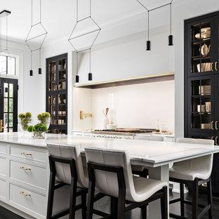 Modern inredning av ett stort vit vitt kök, med vitt stänkskydd, vita vitvaror, mörkt trägolv, en köksö, en undermonterad diskho, luckor med infälld panel, vita skåp, bänkskiva i kvartsit, stänkskydd i sten och brunt golv