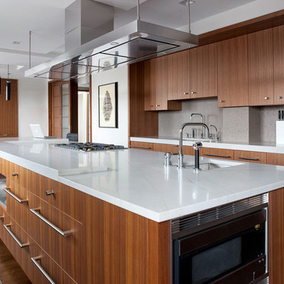 Trendy galley eat-in kitchen photo in Boston with an undermount sink, flat-panel cabinets, medium tone wood cabinets, gray backsplash, stainless steel appliances and an island