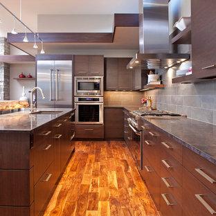 Idée de décoration pour une cuisine design en L avec un placard à porte plane, des portes de placard en bois sombre, une crédence grise et un électroménager en acier inoxydable.