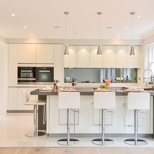 Medium sized contemporary u-shaped kitchen/diner in Berkshire with flat-panel cabinets, white cabinets, quartz worktops, mirror splashback, a breakfast bar, metallic splashback, beige floors and grey worktops.