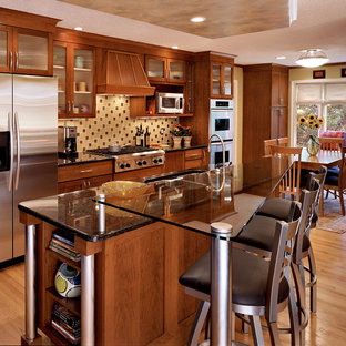 Large transitional eat-in kitchen ideas - Eat-in kitchen - large transitional galley light wood floor eat-in kitchen idea in Bridgeport with glass-front cabinets, medium tone wood cabinets, multicolored backsplash, stainless steel appliances, a double-bowl sink, granite countertops, an island and black countertops