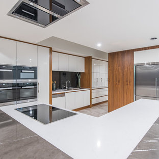 Contemporary u-shaped kitchen in Perth with a drop-in sink, flat-panel cabinets, white cabinets, black splashback, glass sheet splashback, stainless steel appliances, with island, grey floor and white benchtop.