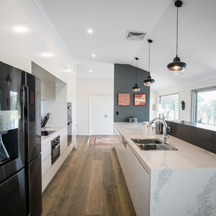 Photo of a contemporary galley kitchen in Sydney with a drop-in sink, flat-panel cabinets, white cabinets, black appliances, medium hardwood floors, a peninsula, brown floor and grey benchtop.