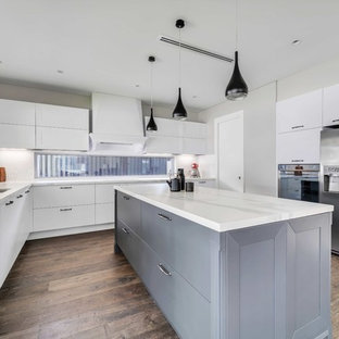 Design ideas for a contemporary u-shaped kitchen in Sydney with a double-bowl sink, flat-panel cabinets, white cabinets, white splashback, stainless steel appliances, medium hardwood floors, with island, brown floor and white benchtop.