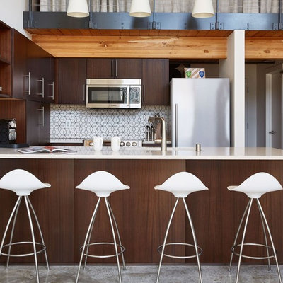 Example of a small trendy u-shaped open concept kitchen design in Seattle with quartzite countertops, white backsplash, flat-panel cabinets, dark wood cabinets, stainless steel appliances and a peninsula