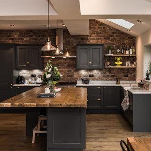 Idéer för att renovera ett mellanstort vintage kök, med en rustik diskho, en köksö, skåp i shakerstil, svarta skåp, stänkskydd i tegel, mellanmörkt trägolv och marmorbänkskiva