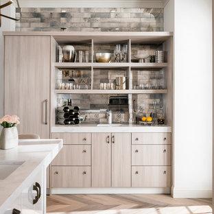 ローリーの中サイズのコンテンポラリースタイルのおしゃれなキッチン (フラットパネル扉のキャビネット、淡色木目調キャビネット、シルバーの調理設備の、メタリックのキッチンパネル、ミラータイルのキッチンパネル、人工大理石カウンター、アンダーカウンターシンク、無垢フローリング、茶色い床) の写真